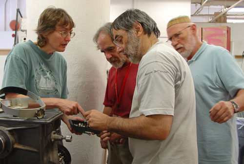 Shop supervisor Jane Swanson discusses installation of the Stubby lathe motor with Sean, Jean-François, and Siegfried.