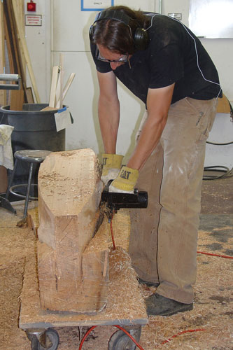 Peter shapes the log for his bench with a chainsaw.