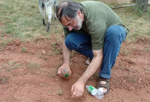 Jean-Françoiso collects some red dirt.