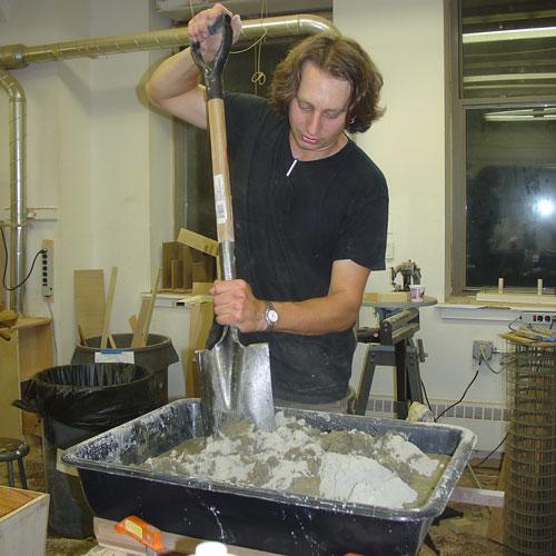Peter mixes the concrete.