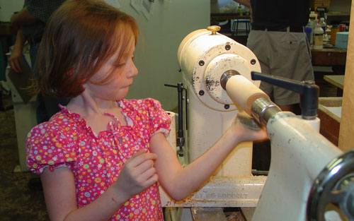 Gianna learns to sand on the lathe.