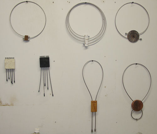Two small wall pieces and some cable-and-wood necklaces.