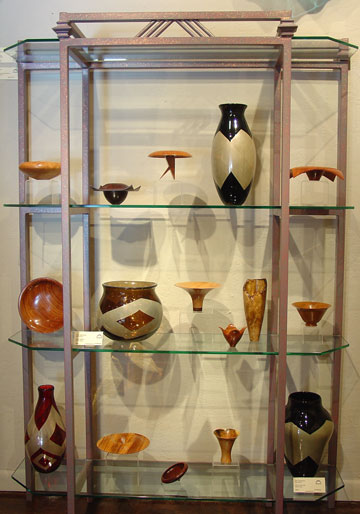 Pieces on shelves in the second room, intermixed with large glass vessels.